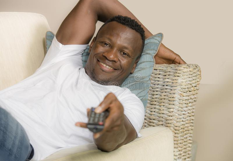 Attractive and happy black afro American man relaxed at home sofa couch enjoying watching television sports or movie smiling. Lifestyle portrait young attractive royalty free stock photography