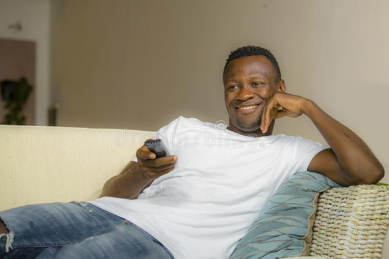 Attractive and happy black afro American man relaxed at home sofa couch enjoying watching television sports or movie smiling. Lifestyle portrait young attractive stock photos