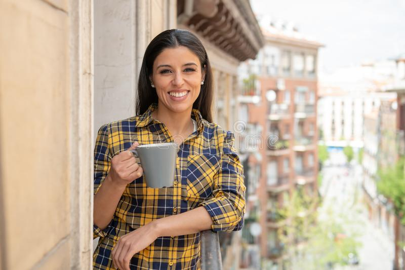 Attractive happy casual young woman relaxing drinking coffee at home enjoying the view on a balcony. Morning coffee. Happy beautiful latin woman smiling and stock photography