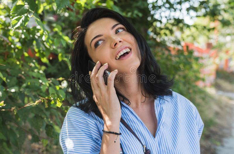 Attractive happy cheerful young Caucasian woman with charming smile wearing blue shirt talking on mobile phone about the planinng stock photography
