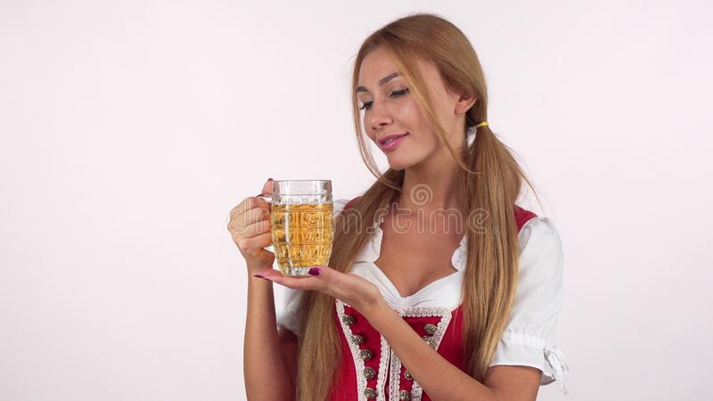 Attractive happy german woman in Oktoberfest costume serving mug of beer. Beautiful happy Bavarian waitress holding delicious beer. Service, profession, job royalty free stock photography