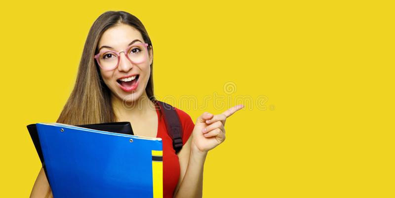 Attractive happy girl being in high spirit after classes, opens mouth and exclaims from happiness, points with index finger at. Copy space for your promotion stock images
