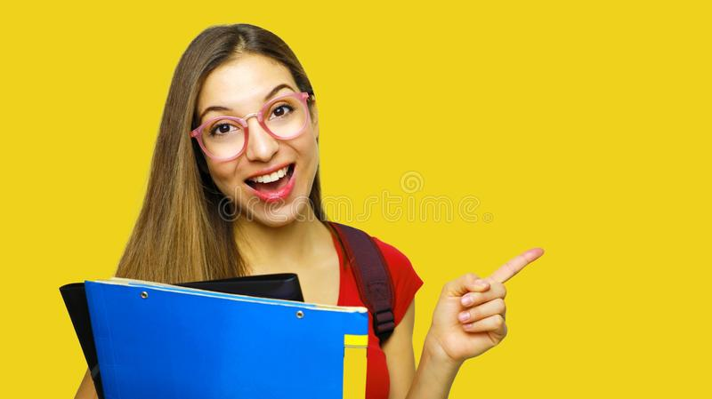 Attractive happy girl being in high spirit after classes, opens mouth and exclaims from happiness, points with index finger at. Copy space for your promotion royalty free stock photo