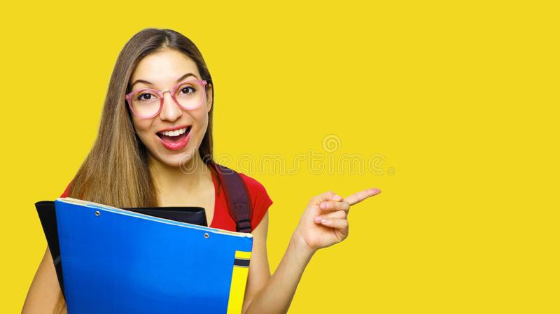 Attractive happy girl being in high spirit after classes, opens mouth and exclaims from happiness, points with index finger at. Copy space for your promotion royalty free stock image