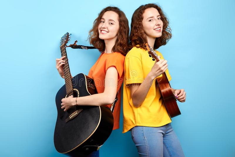 Attractive happy girls singing songs and playing the instrument royalty free stock images