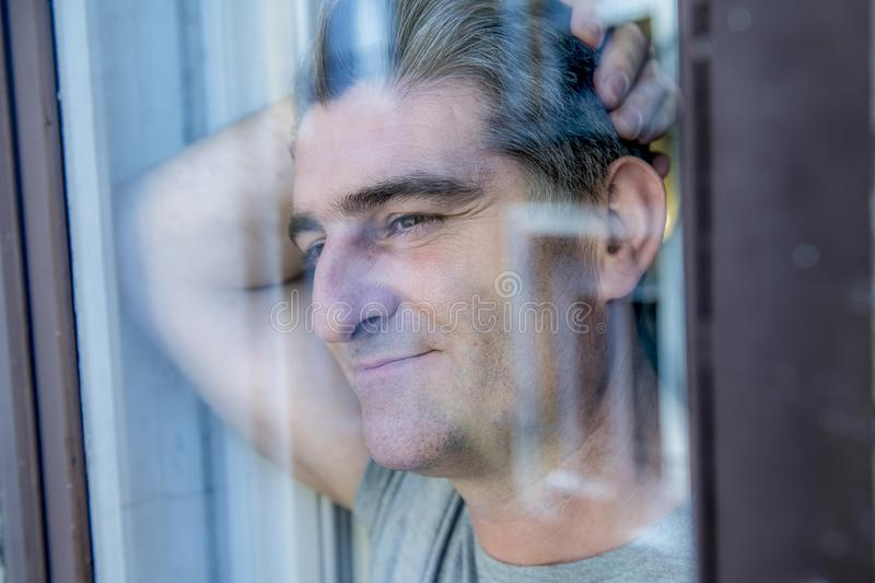 Attractive and happy grey hair man on his 40s or 50s looking throw window glass leaning tranquil and satisfied looking thoughtful. And daydreaming at home in stock photography