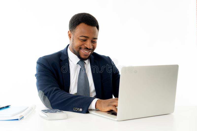 Attractive happy handsome african american businessman working on laptop computer on desk at office royalty free stock photos