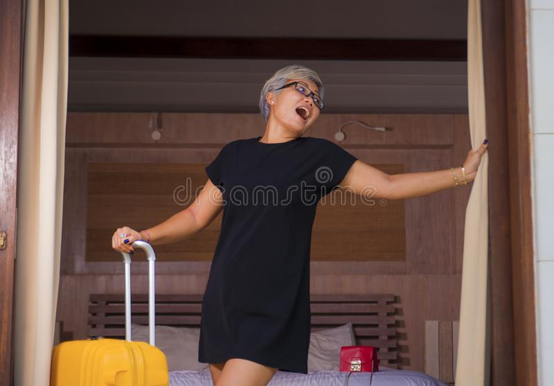 Attractive and happy middle aged Asian woman in stylish Summer dress arriving to hotel opening room balcony door looking delighted stock photography