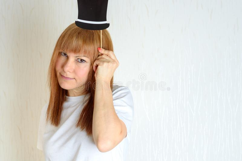 Attractive happy middle aged woman having fun with a fake hat on stick. Female in the period menopause. Lifestyle, Women`s Health concept. Image can be used to stock photos