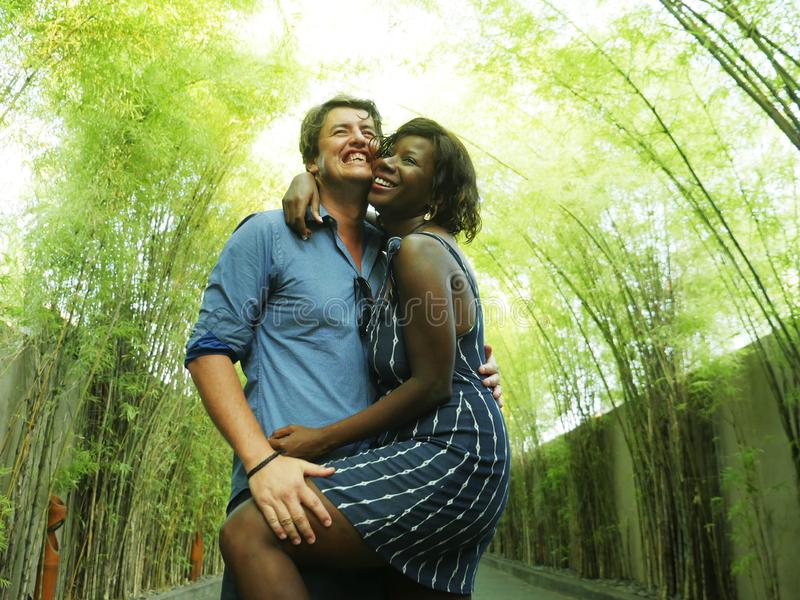 Attractive and happy mixed ethnicity couple cuddling with attractive black afro American girlfriend or wife and handsome Caucasian stock image