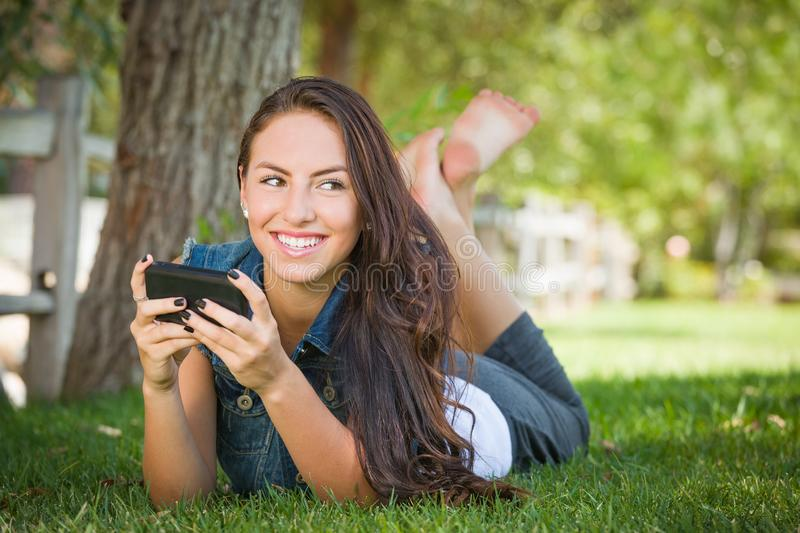 Attractive Happy Mixed Race Young Female Texting on Her Cell Phone Outside Laying in the Grass stock photos