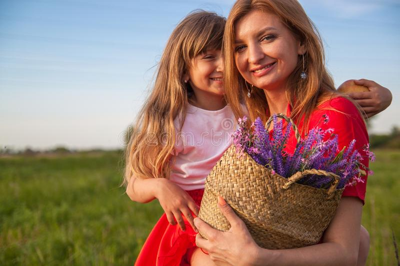 A portrait of Happy mother and daughter in green field in nature in summer. Nature, happiness. royalty free stock photos