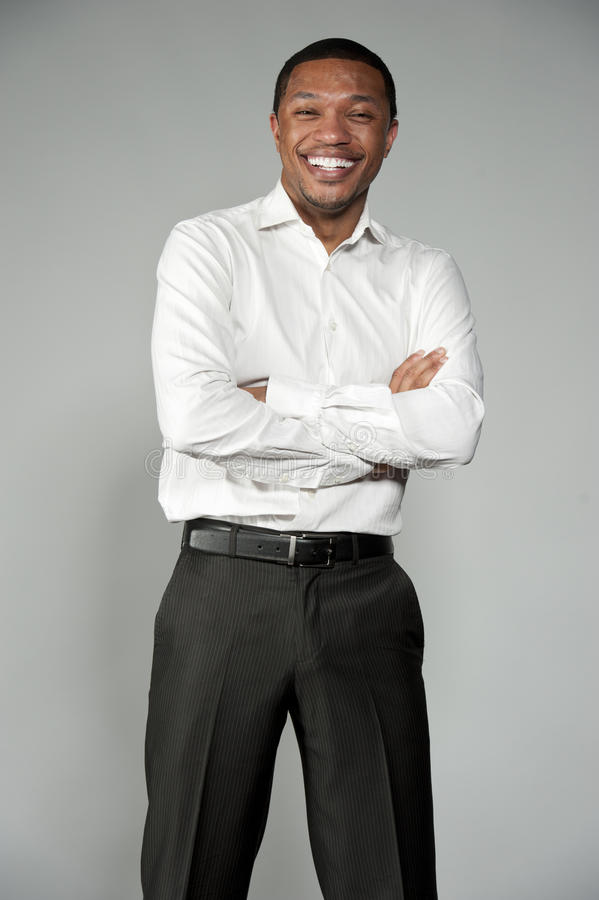 Attractive Happy Professional Young Black Male. An attractive and happy African American boy wearing a white button down and black slacks on a gray background in royalty free stock photo