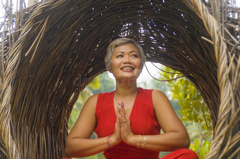 Attractive and happy 40s or 50s middle aged Asian woman in classy and beautiful red dress practicing yoga relaxation and stock image