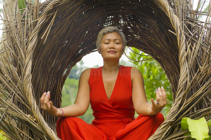 Attractive and happy 40s or 50s middle aged Asian woman in classy and beautiful red dress practicing yoga relaxation and. Outdoors natural portrait of attractive royalty free stock image