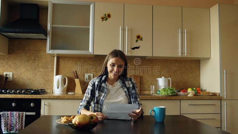 Attractive happy woman recieve good news reading letter in the kitchen while have breakfast at home early morning stock images
