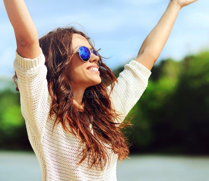 Attractive happy woman in sunglasses enjoying freedom outdoors w. Attractive happy woman in sunglasses enjoying freedom outdoors stock image