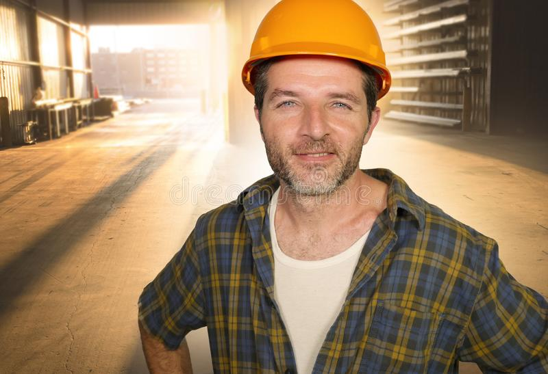Attractive and happy workman in safety helmet smiling confident posing relaxed as successful contractor or handyman at warehouse stock images