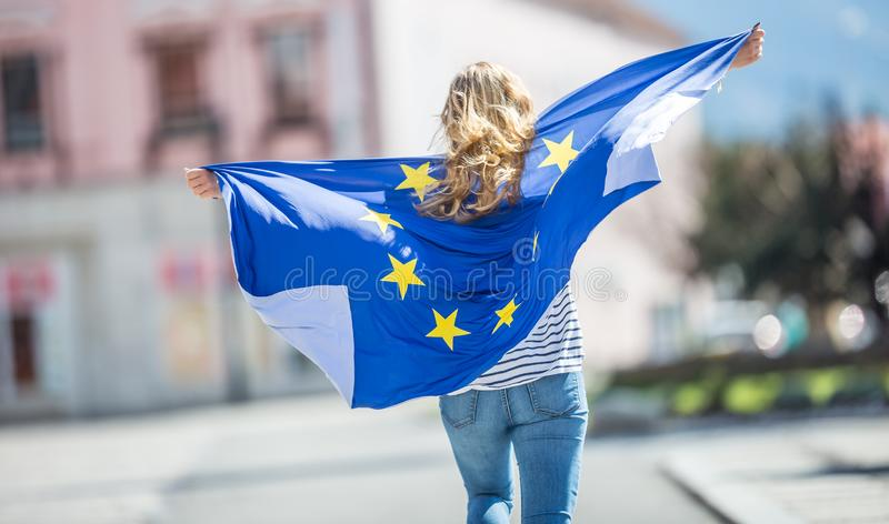 Attractive happy young girl with the flag of the European Union. Student woman travel destination person people holding cute blue female beautiful portrait royalty free stock image