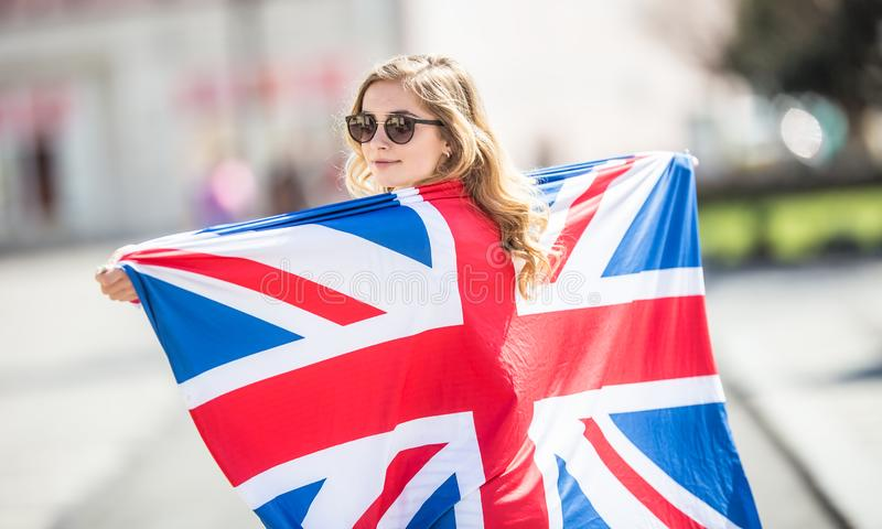 Attractive happy young girl with the flag of the Great Britain royalty free stock images