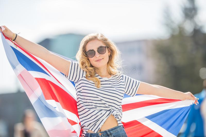 Attractive happy young girl with the flag of the Great Britain stock images