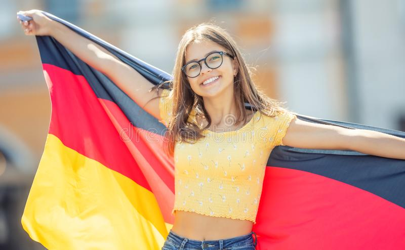 Attractive happy young girl with the germany flag. Person, people, female, european, woman, national, union, smile, travel, portrait, cheerful, fashion royalty free stock photo
