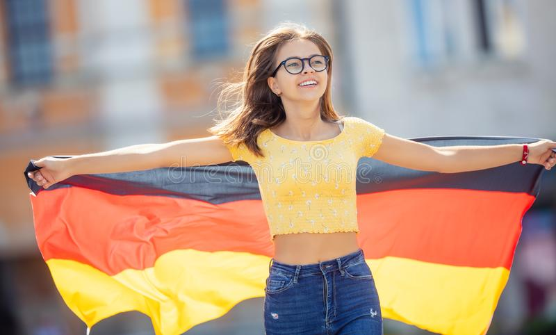 Attractive happy young girl with the germany flag. Person, people, female, european, woman, national, union, smile, travel, portrait, cheerful, fashion royalty free stock photography
