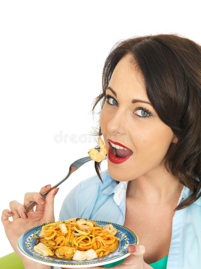 Attractive Happy Young Hispanic Woman Eating a Plate of Seafood Linguine. Beautiful Happy Young hispanic Woman In Her Twenties, eating a Plate of Seafood stock images