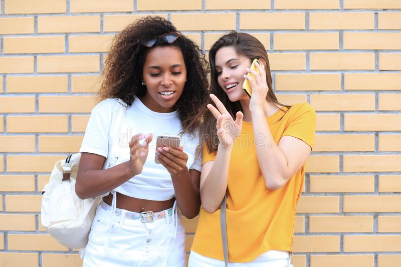 Attractive happy young women friends outdoors using mobile phones chatting royalty free stock photo