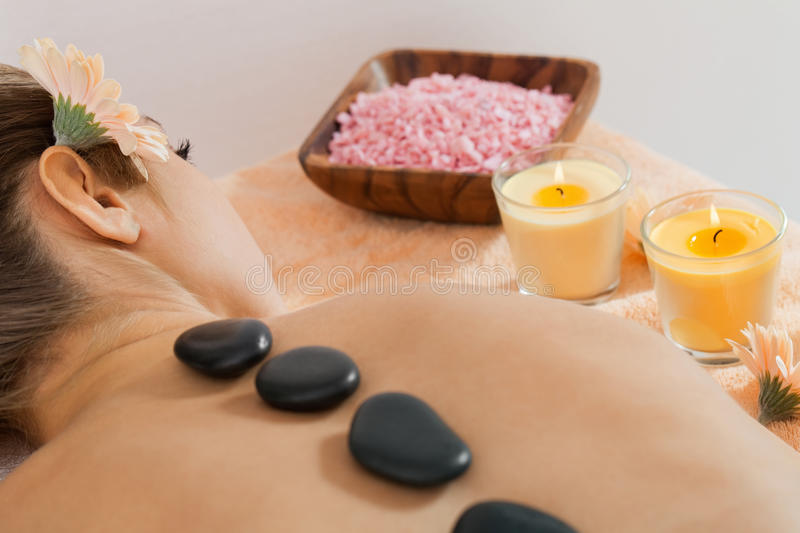 Attractive healthy caucasian woman hot stone massage wellness. Spa therapy royalty free stock photo