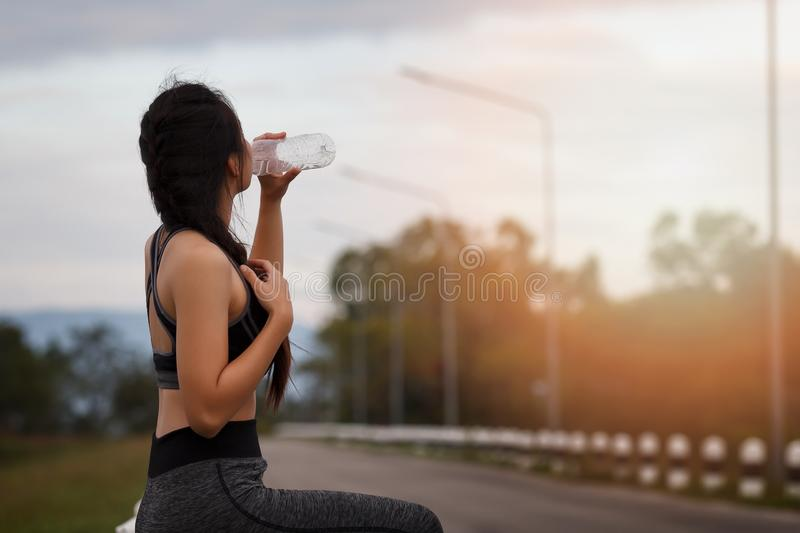 Attractive healthy fitness girl drinking water after workout. Runner girl take a rest after training stock images