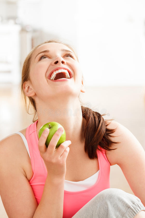 Attractive healthy happy young woman holding green apple. Pretty healthy young woman holding a green apple smiling stock images