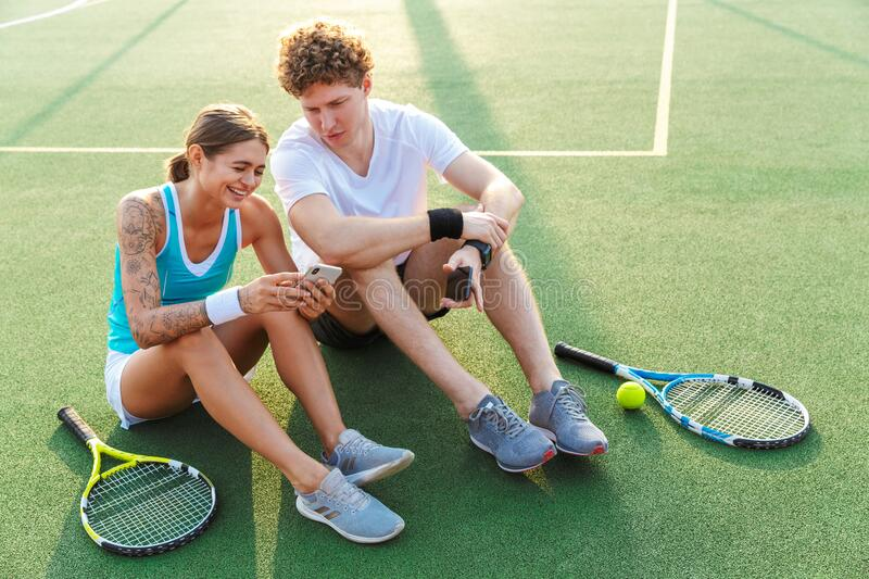 Attractive healthy tennis players couple using mobile phones royalty free stock images