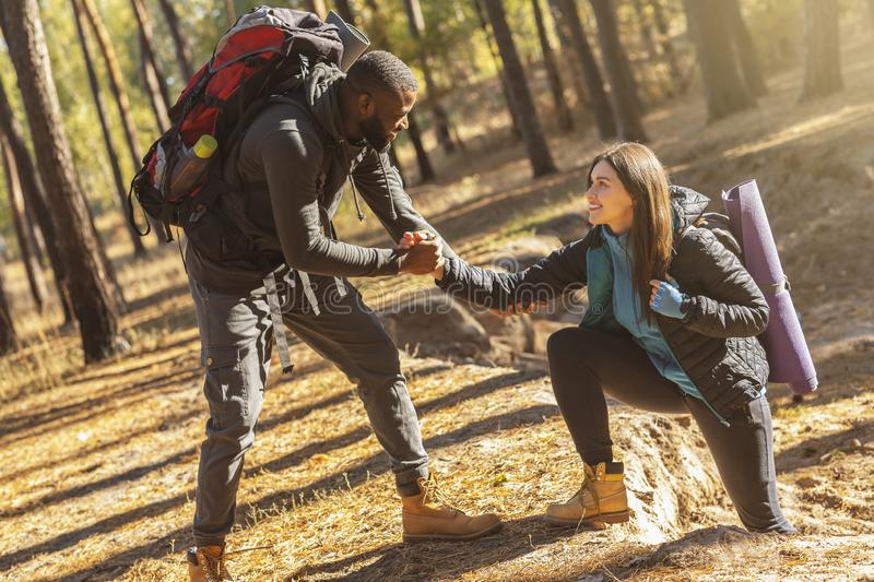 Attractive hiker helping his girlfriend uphill in the countryside. Attractive african hiker helping his girlfriend uphill in the countryside royalty free stock image