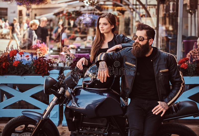 Attractive hipster couple - bearded brutal male in sunglasses dressed in a black leather jacket and his young sensual royalty free stock photos
