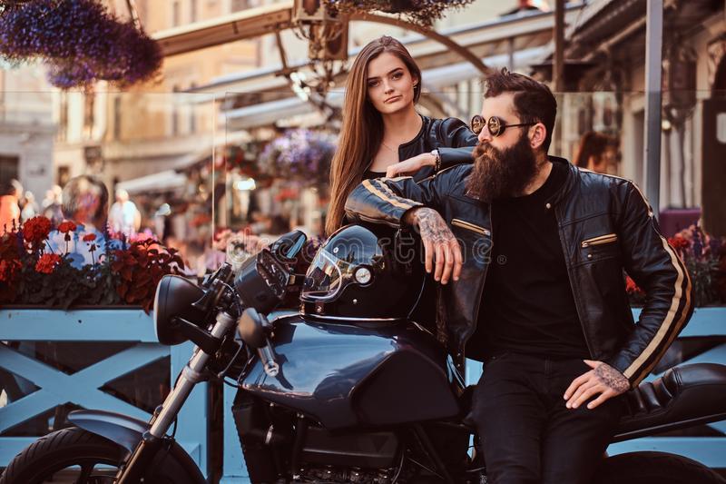 Attractive hipster couple - bearded brutal male in sunglasses dressed in a black leather jacket and his young sensual royalty free stock photography