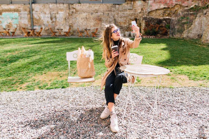 Attractive hipster girl wearing beige coat makes selfie for instagram profile during coffee break in outdoor cafe. Young. Stylish woman taking pictures of stock photography