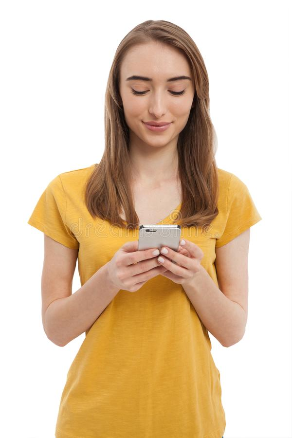 Attractive hipster girl wearing yellow t-shirt and texting on smartphone isolated on white. Copy space.mock up. Summer blank shirt royalty free stock photo