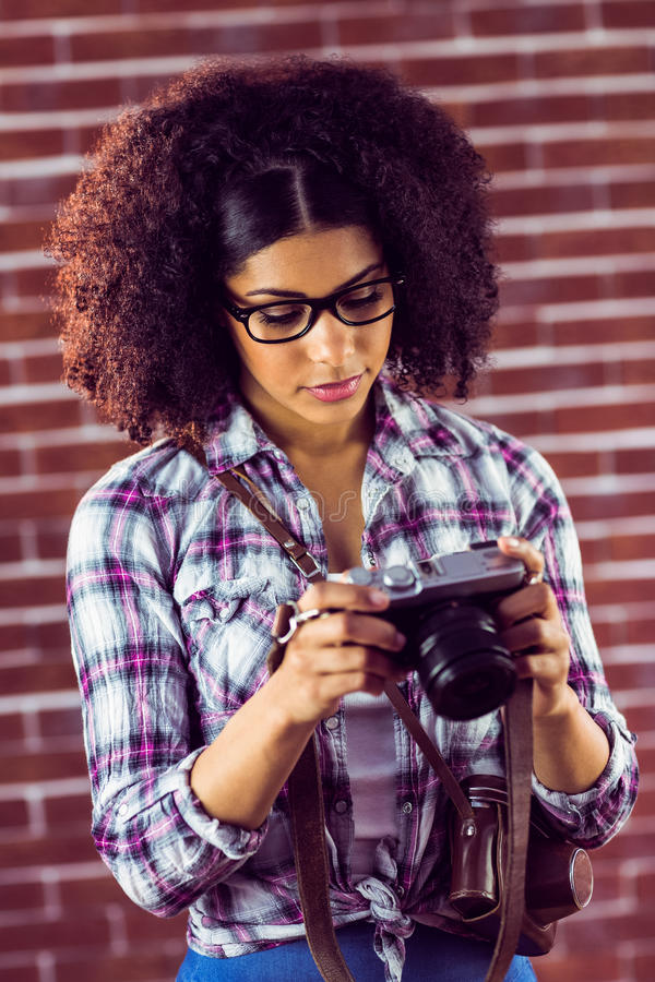 Attractive hipster looking at photos on camera stock images