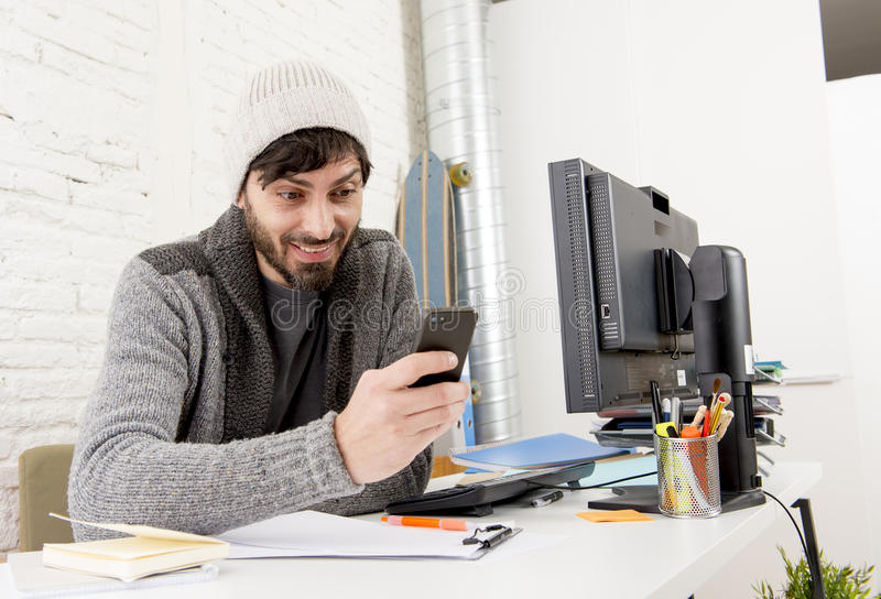 Attractive hipster trendy creative designer using internet in mobile phone smiling confident. Young attractive man in hipster beanie and trendy style businessman royalty free stock image