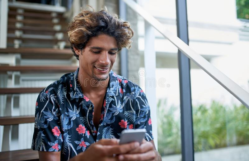 Attractive hispanic hipster millennial influencer smiling and texting on cellphone sitting on modern stairs of bright royalty free stock images