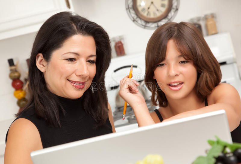 Attractive Hispanic Mother & Daughter Using Laptop Royalty Free Stock Images