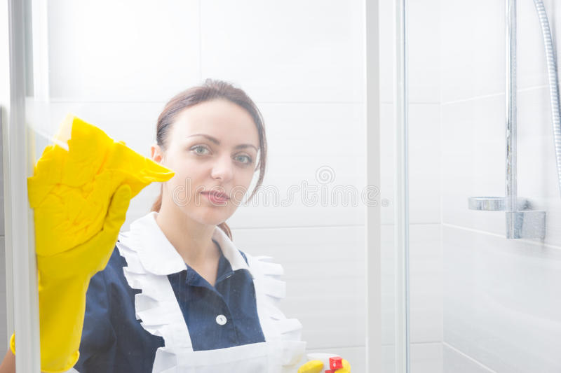 Attractive housekeeper or maid cleaning a shower stock images