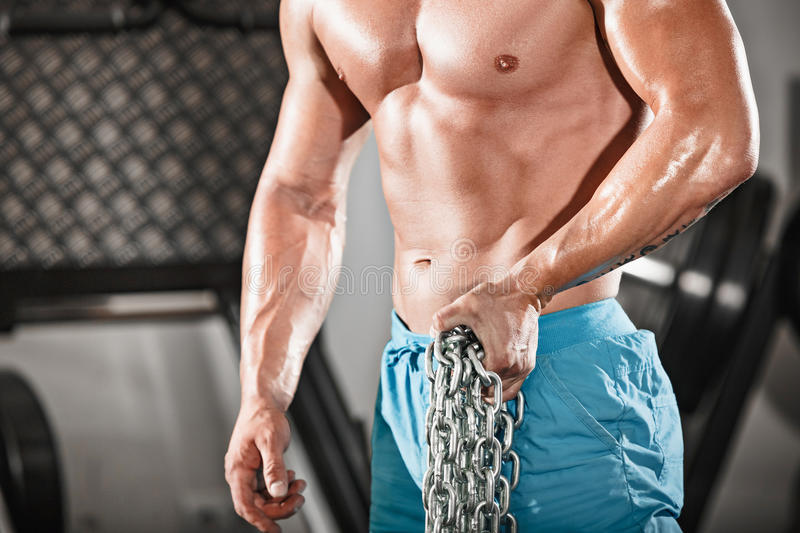 Attractive hunky black male bodybuilder doing bodybuilding pose in gym with iron chains. Over shoulders stock photography