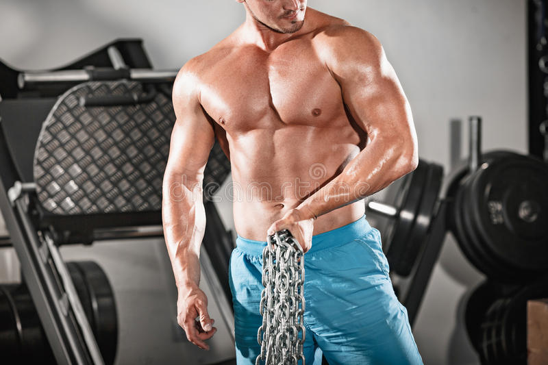 Attractive hunky black male bodybuilder doing bodybuilding pose in gym with iron chains. Over shoulders royalty free stock photography