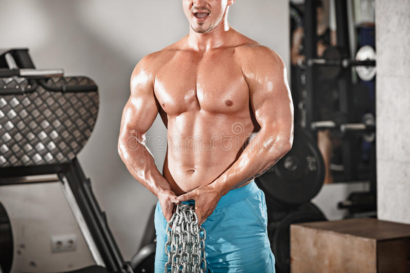 Attractive hunky black male bodybuilder doing bodybuilding pose in gym with iron chains. Over shoulders royalty free stock photos