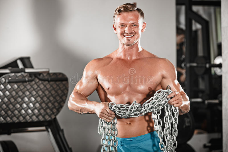 Attractive hunky black male bodybuilder doing bodybuilding pose in gym with iron chains. Over shoulders stock images