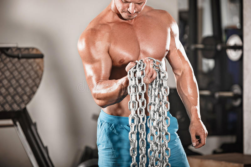 Attractive hunky black male bodybuilder doing bodybuilding pose in gym with iron chains. Over shoulders royalty free stock image