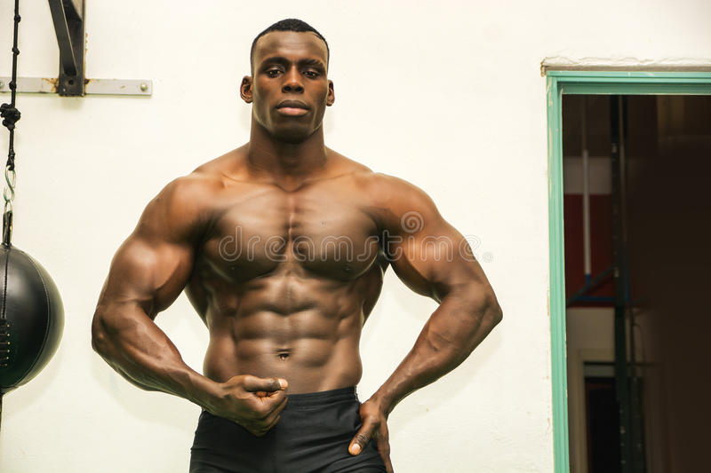 Attractive hunky black male bodybuilder in gym stock photo