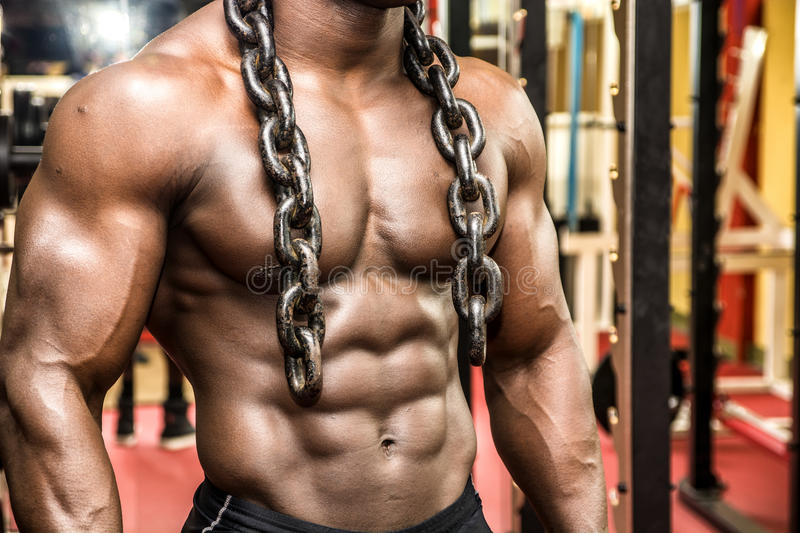 Attractive hunky black male bodybuilder posing with iron chains. Attractive hunky black male bodybuilder doing bodybuilding pose in gym with iron chains over stock images